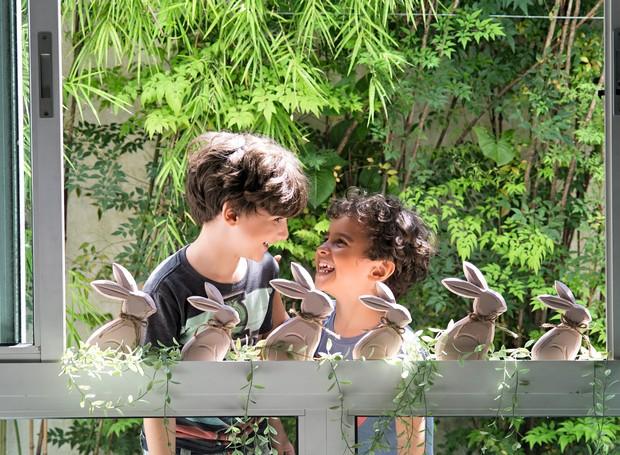 Os irmãos Caiubi e Iamandu se divertem atrás da janela decorada com coelhinhos de madeira e heras Villa Pano (Foto: Cacá Bratke / Editora Globo)