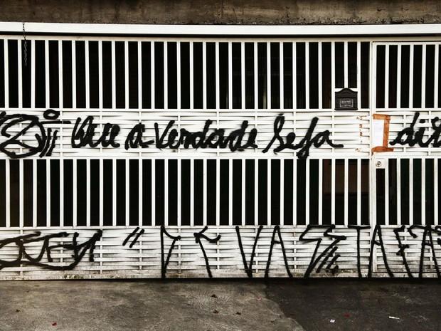 """O muro e o portão da casa onde morava a família morta na madrugada de segunda-feira (5), na Brasilândia, Zona Norte da capital, amanheceram pichados nesta sexta-feira (9). A frase legível no portão diz """"que a verdade seja dita"""". (Foto: Renato Ribeiro/Futura Press/Estadão Conteúdo)"""