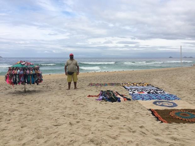 Vendedor de canga e biquínis desde 2001, Reisnan Araújo, de 28 anos, culpa a baixa temperatura pelas vendas fracas.  (Foto: Cristiane Caoli / G1)