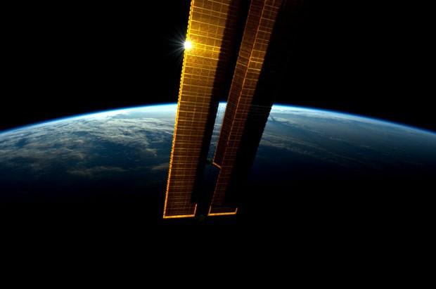 Sol reflete nos painéis solares da Estação Espacial Internacional durante o amanhecer. A foto foi tomada pelo astronauta Andre Kuipers em 8 de junho e divulgada nesta quarta (13) (Foto: Andre Kuipers/Nasa/AP)