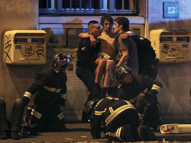 Equipe de resgate carrega um ferido perto da casa de espetáculos Bataclan, em Paris (Foto: Christian Hartmann/Reuters)