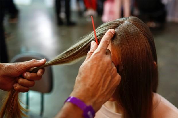 Divida o cabelo ao meio. Escolha um dos lados para começar e separe uma mecha frontal. (Foto: Thiago Bernardes)