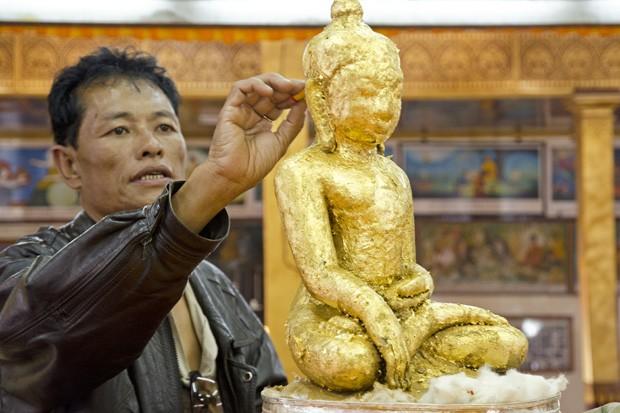 Um fiel coloca uma folha de ouro em umas das cinco figuras de Buda na pagoda Phaung Daw Oo. Este ritual só pode ser realizado por homens (Foto: Haroldo Castro/ÉPOCA)