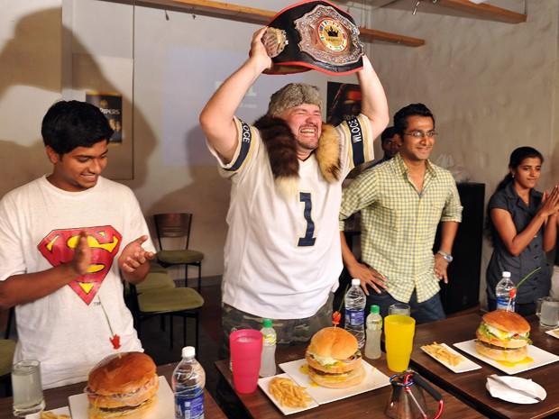 Americano Dale Boone exibe cinturão de campeão mundial do campeonato de 'comilança' antes de início da competição em Bangalore, na Índia, neste domingo (20); ele comeu um hambúrguer de dois quilos em 18 minutos durante o evento (Foto: Manjunath Kiran/AFP)