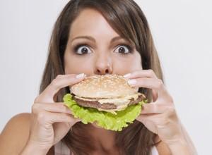 Mulher comendo hambúrguer gula saciedade  (Foto: Getty Images)