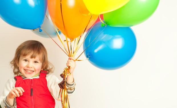 Criança sorrindo e segurando balões (Foto: Shutterstock)