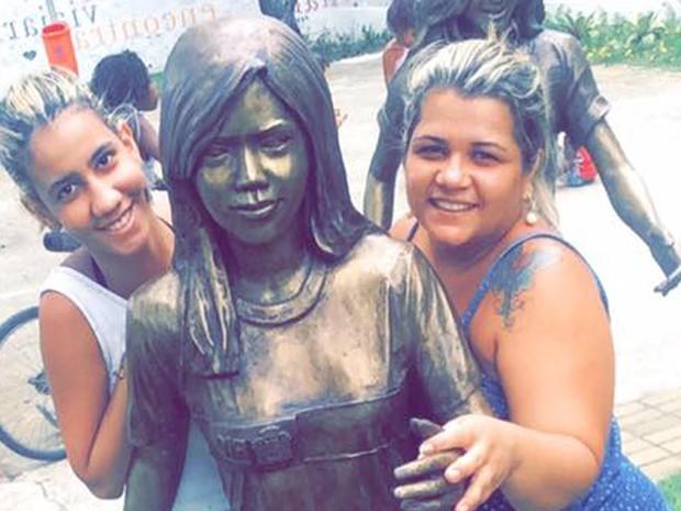 Kelly Guedes, à direita, com a irmã e a estátua que representa Géssica, que perderam no massacre da Escola Tasso da Silveira (Foto: Kelly Guedes/ Arquivo pessoal)