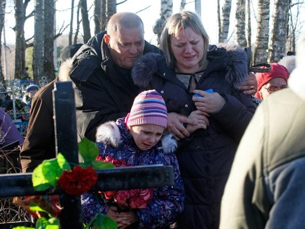 Família de Nina Lushchenko, que tinha 60 anos e trabalhava na cantina de uma escola, no enterro (Foto: Dmitry Lovetsky/AP)
