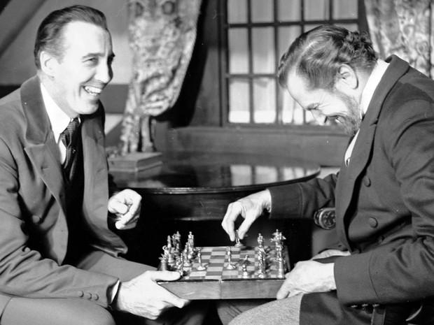 Os atores Christopher Lee (esq.) e Vincent Price riem enquanto jogam xadrez durante gravações de 'O Ataúde do Morto-Vivo', em dezembro de 1968, na Inglaterra (Foto: Bob Dear/AP)