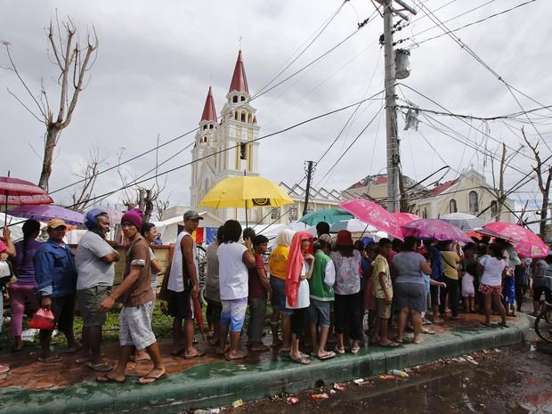 Pessoas fazem fila em frente a um hospital improvisado no pátio da Catedral da cidade de Palo (Foto: Wolfgang Rattay/Reuters)