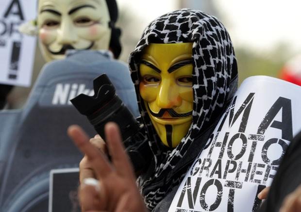 Mascarado segura câmera fotográfica durante protesto (Foto: Hasan Jamali/AP)