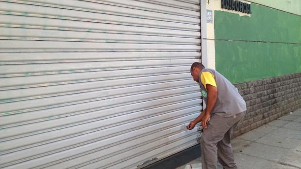 Funcionário pinta porta da loja do Palmeiras, que estava pichada (Foto: Sergio Gandolphi / Globoesporte.com)