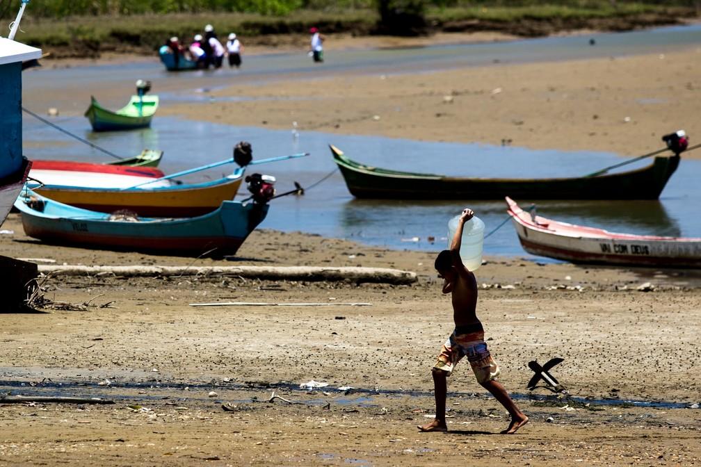 Mar tem avançado sobre as águas do Rio São Francisco, forçando os ribeirinhos a navegar rio acima para conseguir estocar garrafões de água potável (Foto: Jonathan Lins/G1)