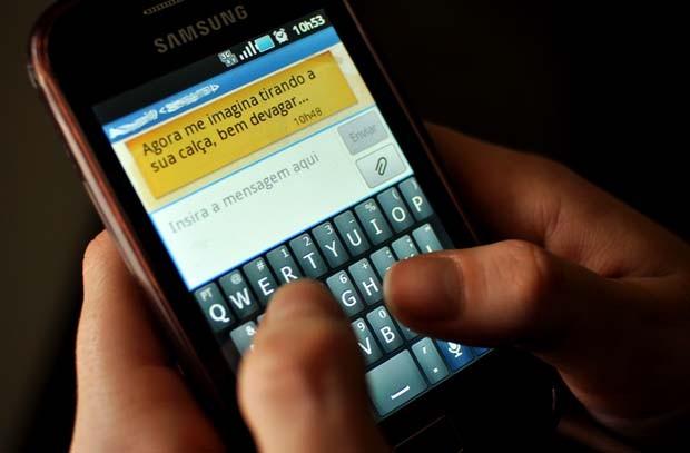 Claudia* simula mensagem sensual que costumava enviar ao namorado (Foto: Guilherme Tosetto)