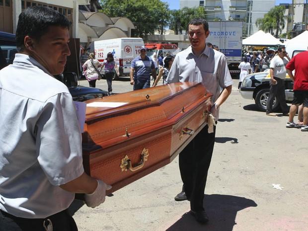 Funcionários de funerária carregam caixão com corpo de vítima de incêndio em Santa Maria (Foto: Reuters)
