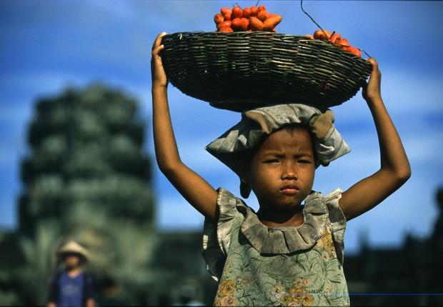 Uma menina carrega uma cesta de frutas na cabeça no Camboja (Foto: Per-Andre Hoffmann/ Gettyimages)