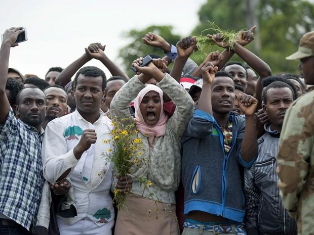 Foto de 2 de outubro mostra moradores de Bishoflu cruzando os punhos como um símbolo do movimento que protesta contra o governo Oromo. A Etiópia declarou estado de emergência neste domingo (9) (Foto: Zacharias Abubecker/AFP)