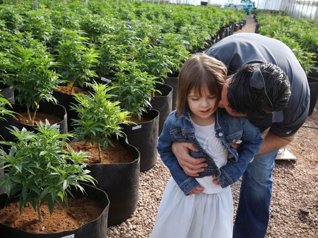 Pai abraça Charlotte Figi em meio a cultivo de plantas de maconha em Colorado (Foto: Brennan Linsley/AP)