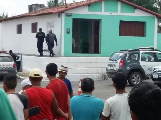 Casa onde o homem atirou na própria mãe está cercada pela polícia (Foto: PM/Divulgação)