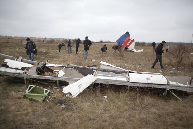 Destroços do voo MH17, que caiu no leste da Ucrânia, são vistos nesta terça-feira (11) durante trabalho de investigadores holandeses no local da queda, perto da vila de Grabove (Foto: Menahem Kahana/AFP)