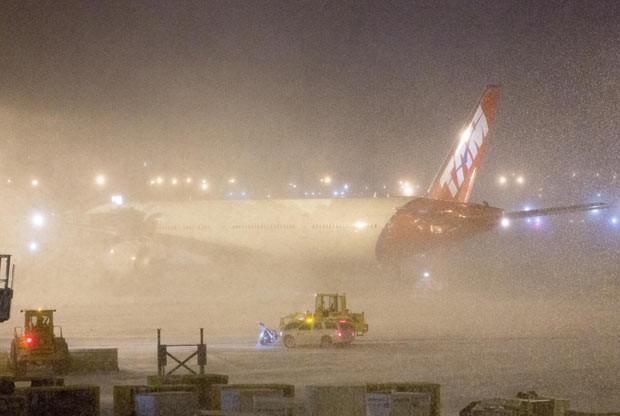 Avião da TAM cercado pela neve nesta terça-feira (21) no aeroporto JFK, em Nova York (Foto: AFP)