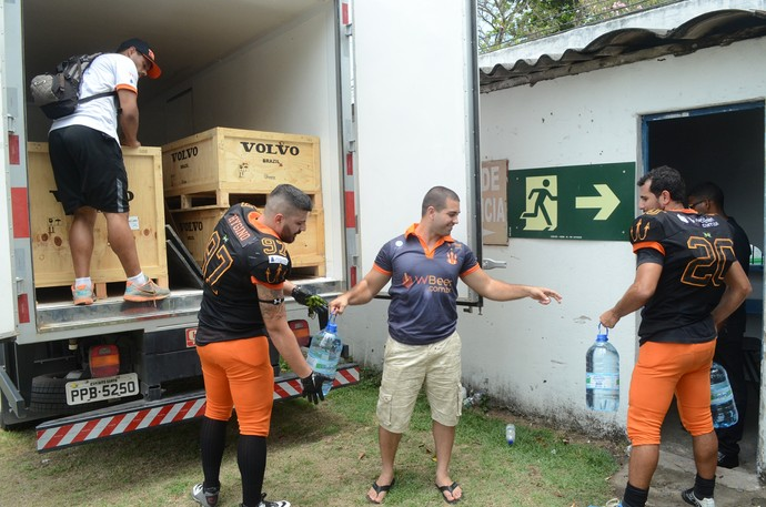 Jogadores do Vila Velha Tritões carregam litros de água doados para as vítimas do desastre embiental (Foto: André Monjardim)