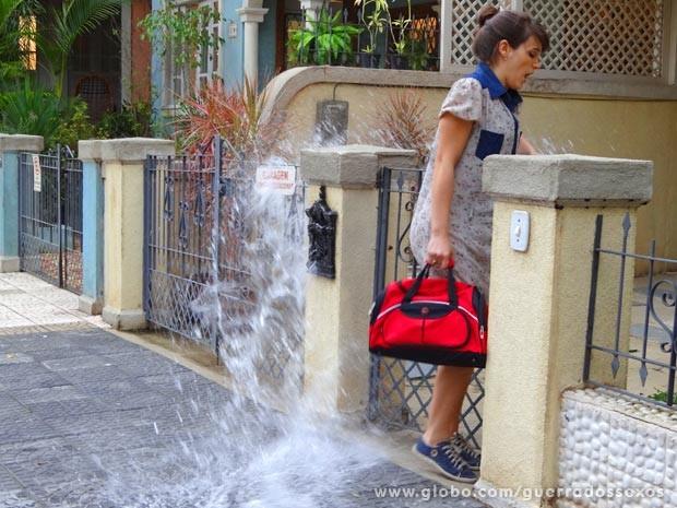 Carolina leva banho de poça ao entrar em casa (Foto: Guerra dos Sexos / TV Globo)