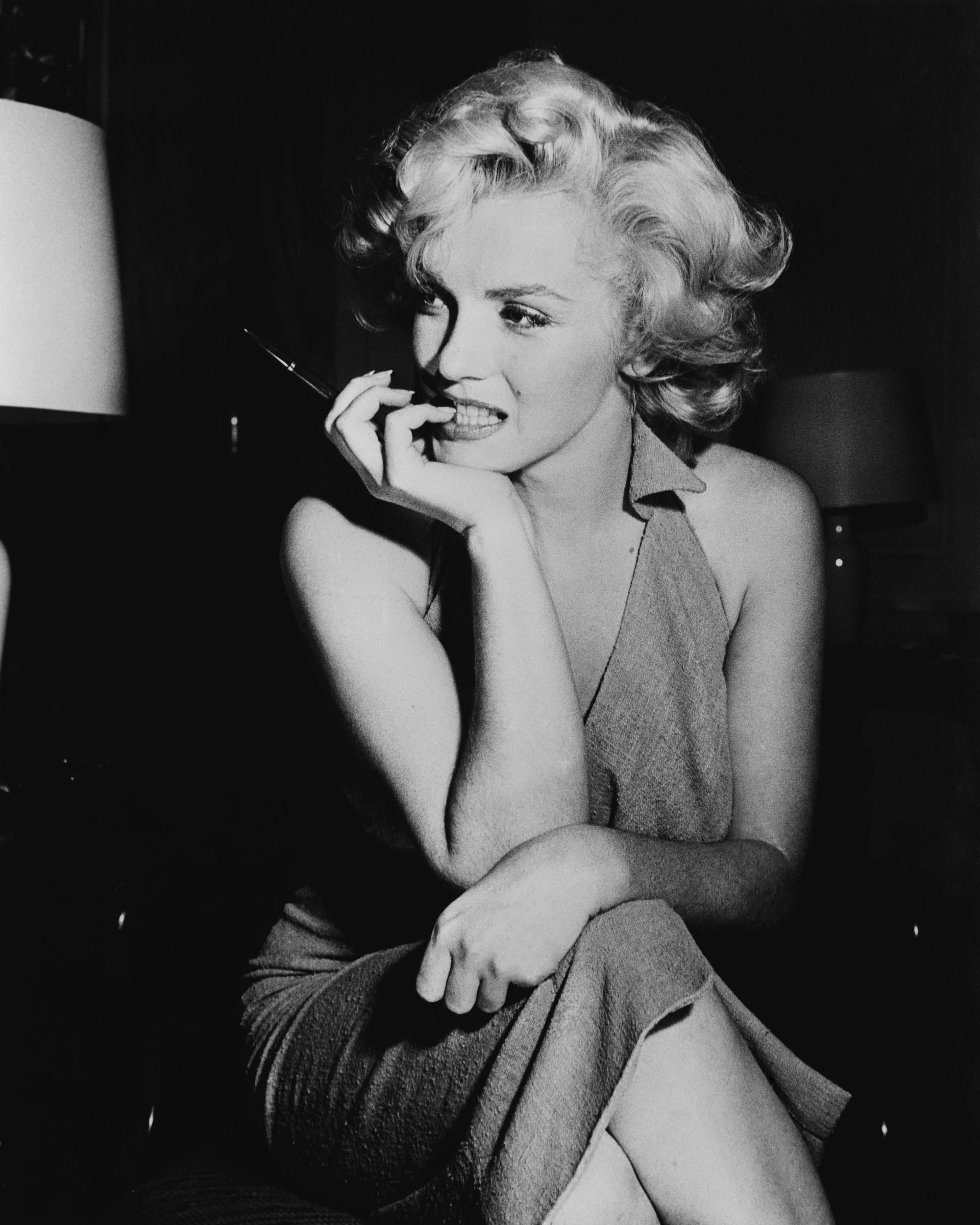 """No dia em que Marilyn foi descoberta deitada nua de cabeça para baixo em seu quarto, segurando o receptor do telefone, o jornal The Los Angeles Times a descreveu como """"beleza perturbada que não conseguiu encontrar a felicidade mesmo sendo a mais brilhante estrela de Hollywood"""". A misteriosa morte aparentou ser suicídio, mas logo teorias começaram a especular que algo de sinistro havia ocorrido: de uma overdose acidental, a morte da sex symbol ganhou ares de conspiração do assassinato do Presidente Kennedy e de seu advogado-irmão, Bobby. Por toda a casa também foram encontradas escutas telefônicas. A ideia de queima de arquivo pode ser reforçada, pois Marilyn daria uma entrevista dali a alguns dias, afirmando que revelaria segredos que interessariam a toda nação. (Foto: Getty Images)"""