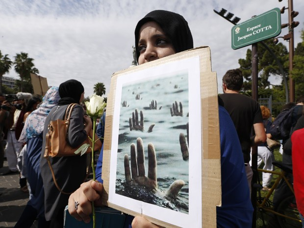 Mulher mostra cartaz , com mãos de pessoas se afogando, durante manifestação em apoio aos migrantes e refugiados em Nice, França, neste sábado (Foto: AFP PHOTO/VALERY HACHE)