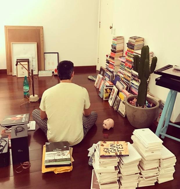 Pedro Neschling entre pilhas de livros antes da mudança (Foto: Reprodução/Instagram)