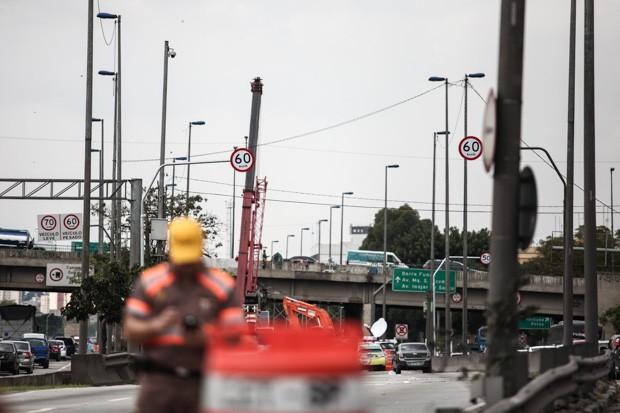 Agente da CET trabalha no local de um acidente na Marginal Tietê. Ao fundo, placas mostram os novos limites nas três vias da Marginal. Na expressa, à esquerda: 70 km/h para veículos leves e 60 km/h para pesados; na central: 60 km/h; na local, à direita: 5 (Foto: Fábio Tito/G1)