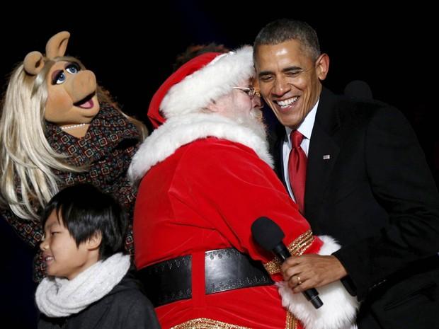 O presidente dos EUA, Barack Obama (dir.), ri ao abraçar o Papai Noel ao lado da personagem Miss Piggy, dos 'Muppets', durante a cerimônia de acendimento da árvore de Natal em Washington DC, na noite de quinta-feira (3) (Foto: Kevin Lamarque/Reuters)