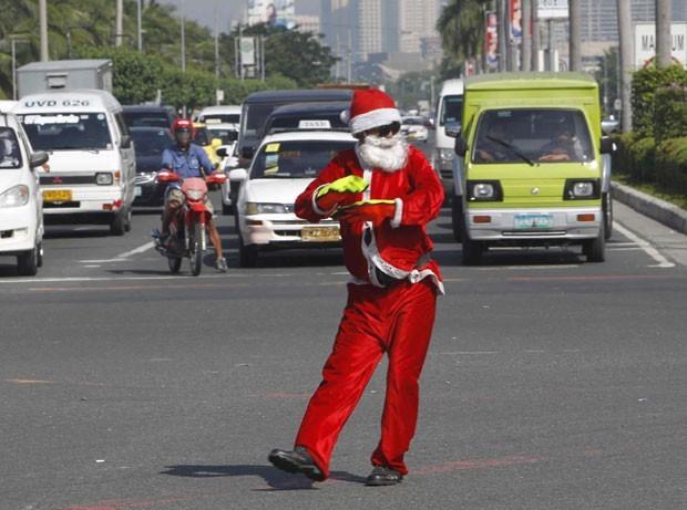 Em novembro, o agente de trânsito Ramiro Hinojas, de 47 anos, foi fotografado usando um traje de Papai Noel enquanto sinalizava o tráfego em uma das principais ruas de Makati City, na região metropolitana de Manila, nas Filipinas. (Foto:  Romeo Ranoco/Reuters)