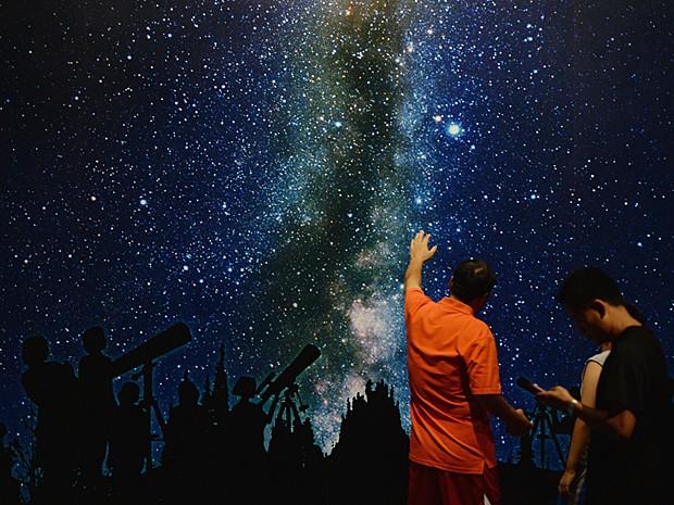 Jovens observam 'céu' estrelado durante exposição nesta sexta-feira (30) (Foto: Mark Ralston/AFP)