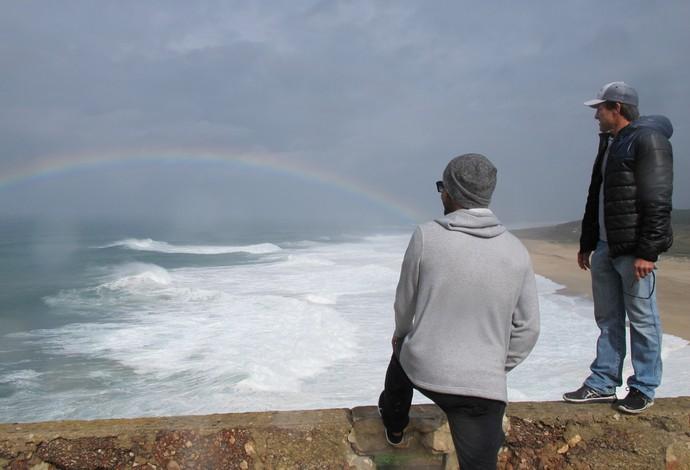 Carlos Burle e Pedro Scooby admiram o arco-íris em Nazaré, após lembrarem de Maya Gabeira (Foto: Carol Fontes)