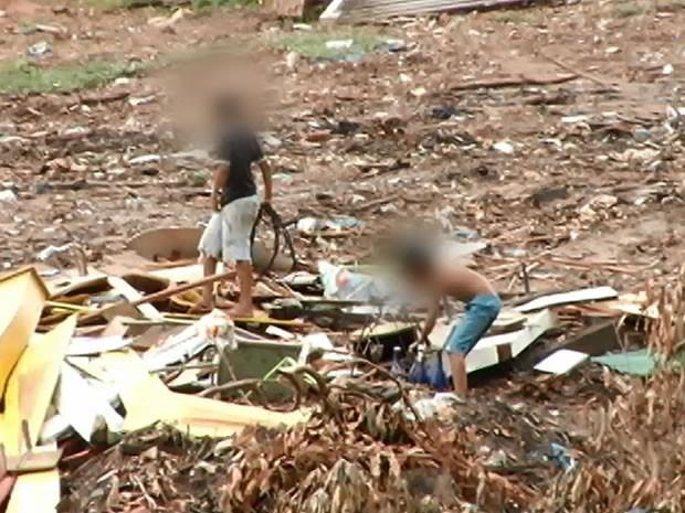 Crianças catam materiais sem se importar com as consequências. (Foto: Reprodução/TV Tapajós)