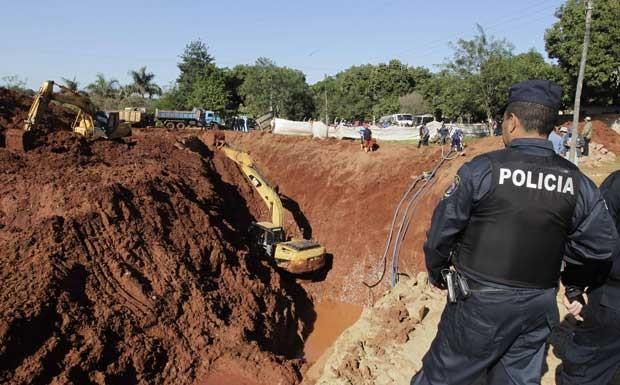 Policiais acompanham escavação de um sítio no Paraguai (Foto: Jorge Adorno/ Reuters)