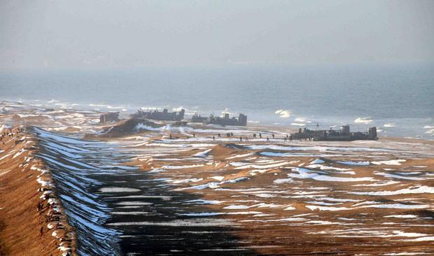 Outra imagem divulgada no mesmo dia pela Coreia do Norte, sem manipulação mais aparente, mostra a chegada à costa, porém com menos embarcações da imagem anterior (Foto: Reuters/KCNA)