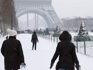 Turistas carregam suas bagagens em um caminho coberto de neve em direção à Torre Eiffel, em Paris  (Foto: John Schults/Reuters)