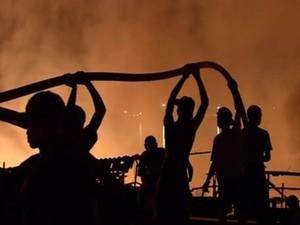 Moradores tentam apagar incêndio na Vila Telma (Foto: Reprodução/TV Tribuna)