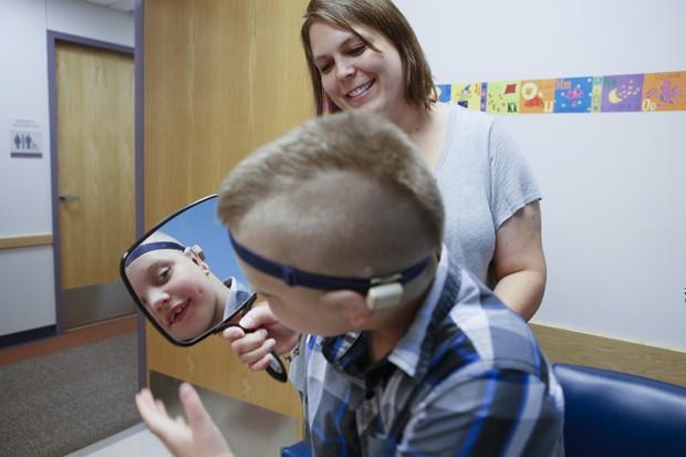 Garoto se olha no espelho para ver suas orelhas novas (Foto: Akron Children's Hospital/Divulgação)
