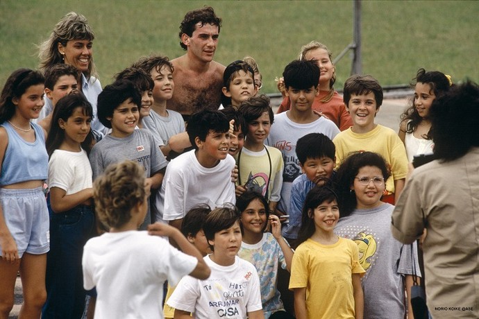 O piloto parou seu treino para tirar fotos com um grupo de crianças, em 1989 (Foto: Norio Koike)