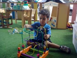 João Pedro brinca com o brinquedo pedagógico montanha-russa (Foto: Alex Araújo/G1)