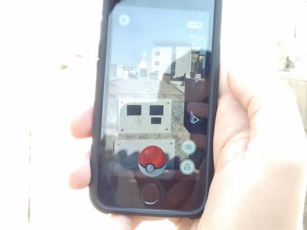 Garoto procura por pokemon entre túmulos em Divinópolis (Foto: Ricardo Welbert/G1)