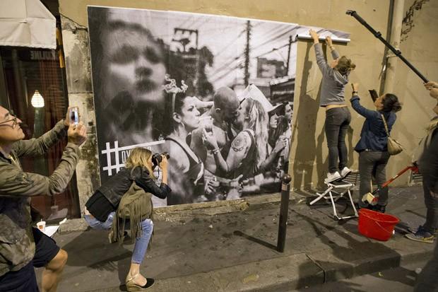 Dysturb cola uma foto gigante feita pela brasileira Alice Martins de torcedores nas ruas de São Paulo durante jogo entre Brasil e México pela Copa do Mundo (Foto: Francois Mori/AP)