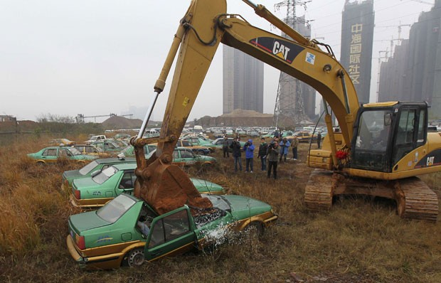 China usou escavadeira para destruir táxis retirados de circulação (Foto: Reuters)