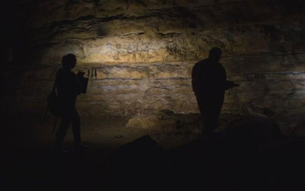 Acompanhada do marido fotógrafo, Genevieve von Petzinger explora a caverna de Cudon, na região espanhola da Cantábria (Foto: BBC/D. von Petzinger)