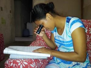 Adrielle usa uma lente de aumento para conseguir enxergar a apostila (Foto: Juliana Borges/ G1 ES)