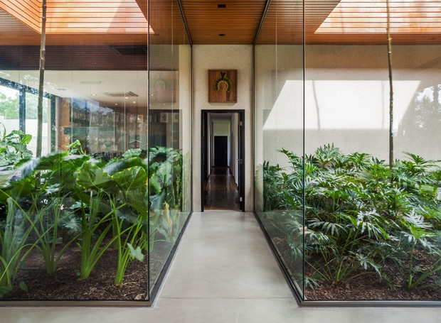 CORREDOR | Para brincar com os limites da construção, os profissionais do escritório FGMF Arquitetos projetaram jardins que invadem os espaços internos. Piso Mr Cryl, da Bricolagem, cor cinza natural CPII (Foto: Rafaela Netto/Divulgação)