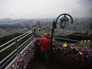 Homem tira foto do mirante, localizado no ponto mais alto da cidade (Foto: Kim Hong-Ji/Reuters)
